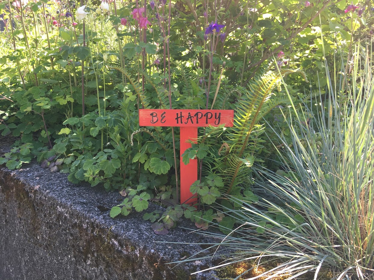 Garden sign that says Be Happy.