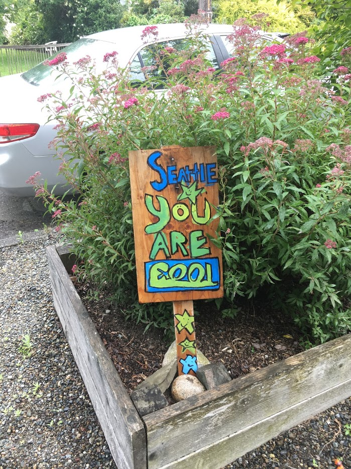 "Wooden sign with words in blue and green that says ""Seattle You Are Cool""."