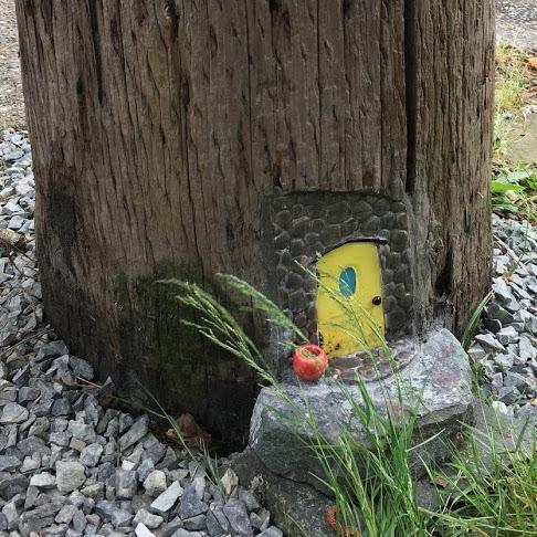 Yellow fairy door in utility pole.