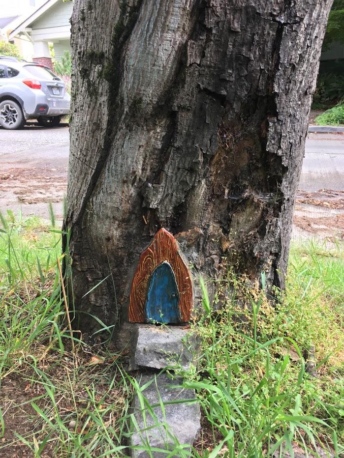 Yard picture: blue ferry door in tree.