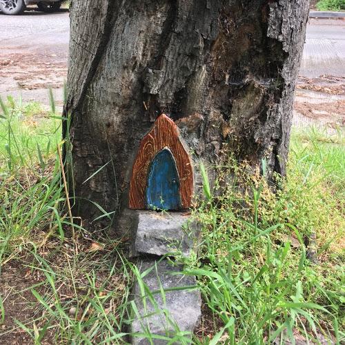Gothic-style fairy door in tree trunk.