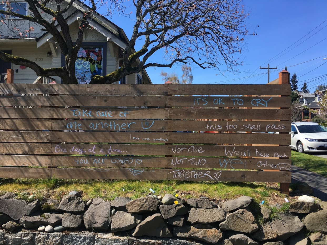Fence with encouraging quarantine messages written in chalk.