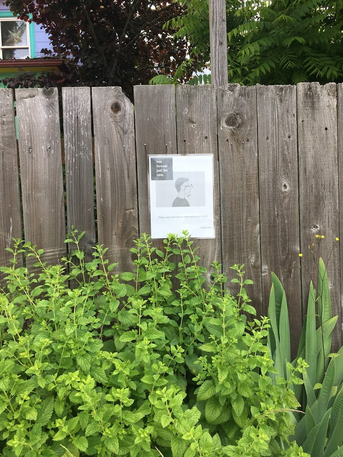 """Mask sign on fence that says """"Not forever, just for now""""."""