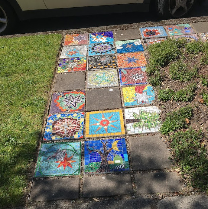 Square mosaics of different pictures in place of cement flagstones as walking path between yard and street.