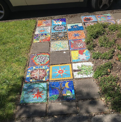 Twenty-two 12-inch mosaics with various pictures on them used to create a sidewalk path.