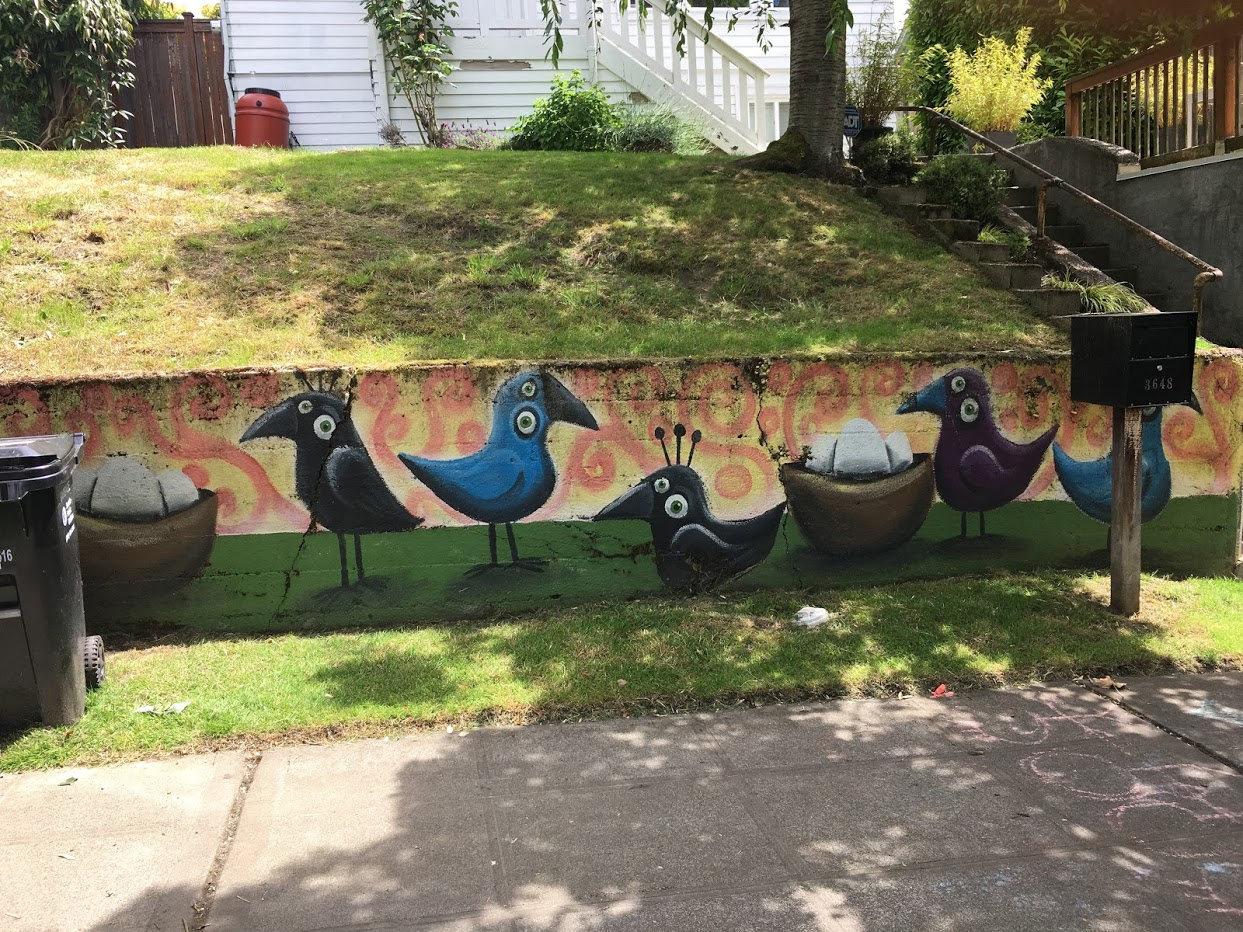 Quirky bird art on concrete retaining wall for a front yard.