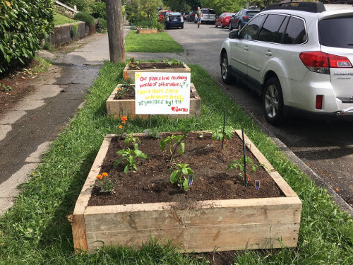 Raised garden bed with sign in it.