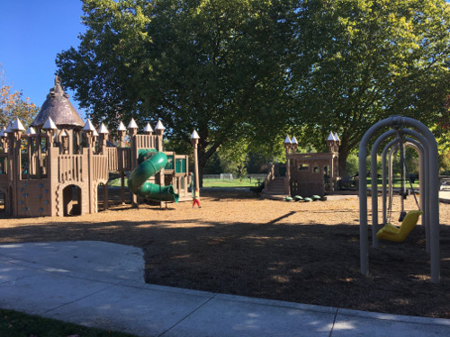 South side of playground with playground structures and swings.