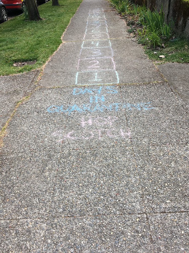 Sidewalk with chalk writing and numbered boxes.