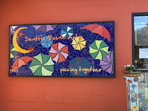 Mosaic on red wall. Blue background with a yellow crescent moon and multi-colored umbrellas. Says Seattle Mosaic Arts piecing together.