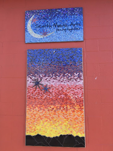 Two mosaics on red wall. Top mosaic shows a crescent moon and says Seattle Mosaic Arts piecing together. Bottom mosaic shows a sunset.