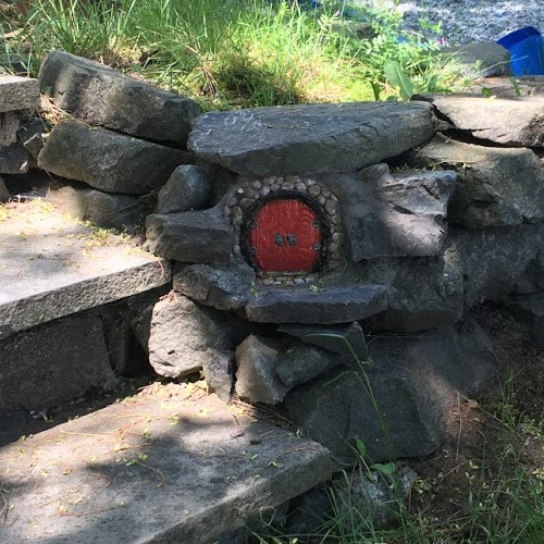 Red round fairy door embedded in stones next to stairs.