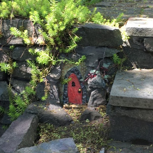 Gothic-style red fairy door embedded in stone next to stairs.