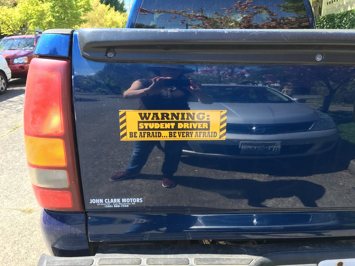 "Bumper sticker on truck says ""Warning: Student Driver. Be Afraid . . . . Be Very Afraid""."