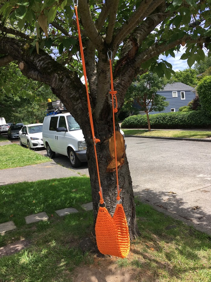 Orange crocheted (or knitted?) swing hanging from tree.