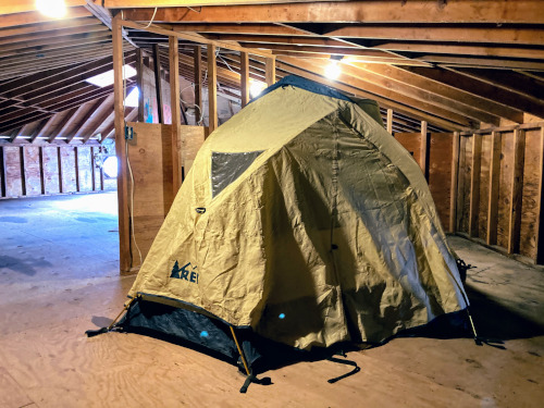 REI brand tent, with rain fly on, setup in an unfinished garage.