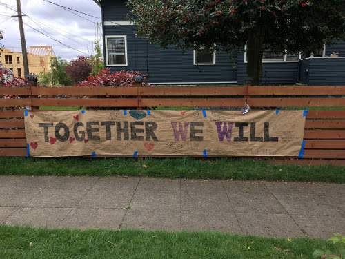 "Sign on fence says ""Together We Will"" with smaller, hard to read, writing around the bigger letters."