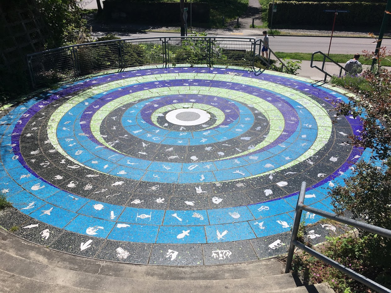 Large circular mosaic on stair langing. Circles of black, blue, green, and purple with marine motifs.